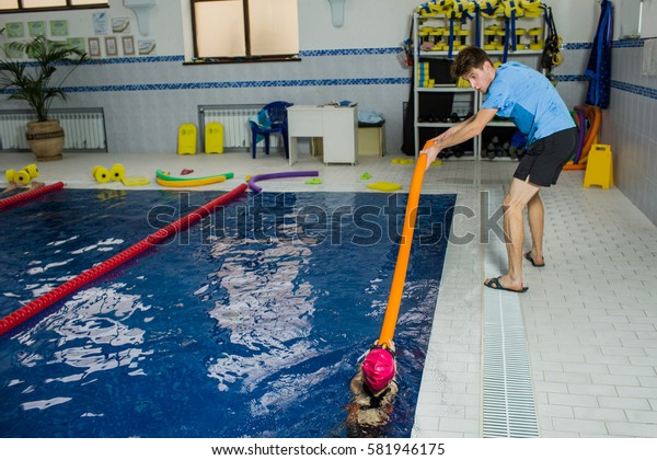 Children's swimming Instructor trains the girl to swim using foam roller at swimming pool