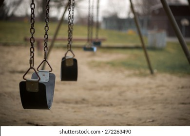 Children's swings hang empty an idle at a playground on a dull, overcast day.