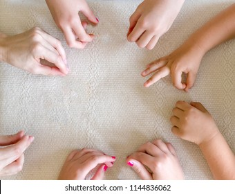 Children's and Teacher's hands together on the table.
