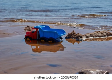 Children's toy bright blue plastic dump truck on the sandy beach of the sea . High quality photo