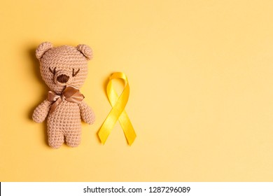 Children's toy with a Childhood Cancer Awareness Yellow Ribbon on yellow background. Childhood Cancer Day February, 15.