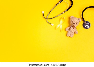 Children's toy with a Childhood Cancer Awareness Yellow Ribbon and stethoscope on yellow background with copy space. Childhood Cancer Day February, 15.
