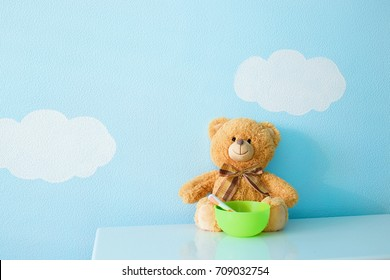Children's toy with the plate. The game is in learning to self-feed. Cheerful and funny baby bear against the background of heaven wallpaper.
