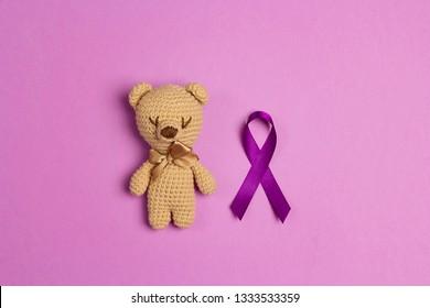Children's toy with a Purple epilepsy awareness ribbon on a purple background. World epilepsy day. Purple Day.