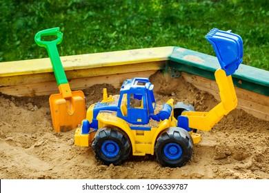 Children's toy tractor in sandbox close up