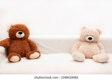 Children's toys - bears of brown and beige color are sitting on the sofa. Selective focus.