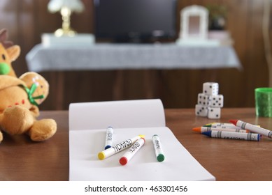 Children's toys, crayons, game pieces and paper on a small table.