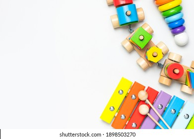 Children's toys made of natural wood on white background. Multi-colored pyramid, train, xylophone in rainbow colors. Eco friendly toy, plastic free. Toy for babies and toddlers. Flat lay top view