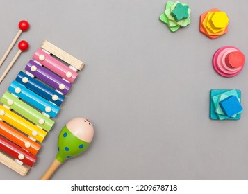 Children's toys: wooden multicolored pyramids, musical instruments maracas and xylophone on a gray background with a place for text. Flat lay, top view