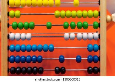 Children's wooden abacus on an orange background.