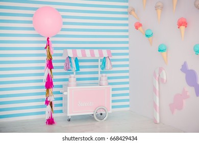 Children's zone with sweets: lollipops, ice cream, macarons, balloon and candy bar. Children room with blue stripe background