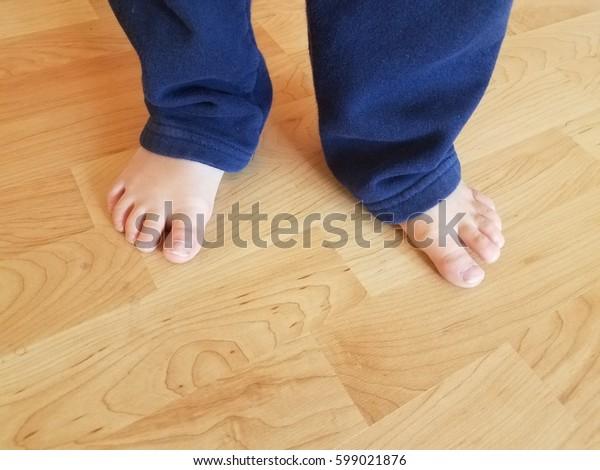 child's bare feet on a wood floor