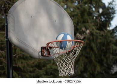 Child's basketball going into weathered hoop