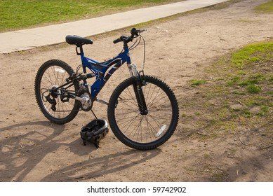 Child's bicycle and helmet standing ready to go on a dirt field by a bike path.