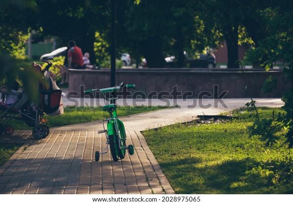childs-bicycle-on-sidewalk-sunlight-600w