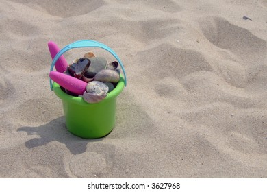 A childs bucket full of stones and seashells at the beach