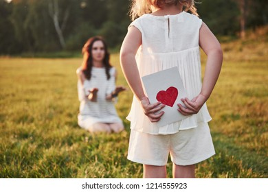 The child's daughter congratulates her mother and gives her a postcard. Mother and girl smile and hug