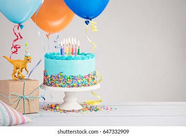 Childs dinosaur themed birthday party with blue cake and colorful balloons over light grey.