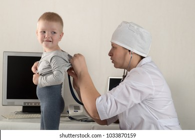 The child's doctor examines patients in his office. Happy children love a good pediatrician very much. Close up of a caucasian woman with a stethoscope. White uniform.