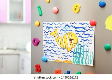 Child's drawing and magnets on refrigerator door in kitchen