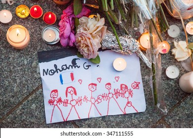 Child's drawing placed at a vigil in Paris in the memory of the victims of terrorist attacks on the 13th November 2015. People with sad faces hold hands in solidarity, with French flag near them