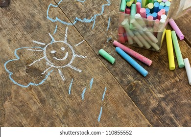 Child's drawings and colored chalk on wooden background