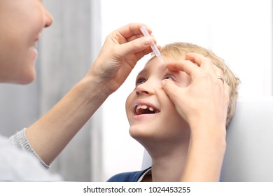 Child's eye drops. The woman lets drops into the child's eye.