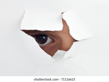 An  child's eye looking through a hole in a  white sheet of paper