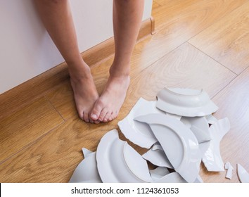 Child's feet and broken dishes.