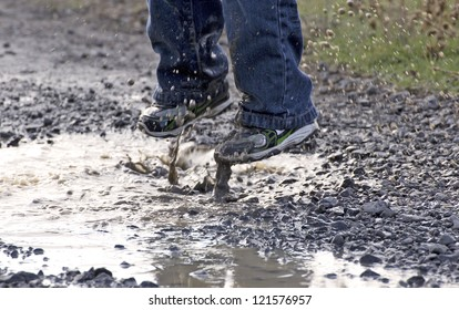 A child's feet as he jumps in to a rain puddle