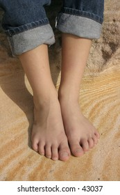 Childs feet on a pattern of sandstone.