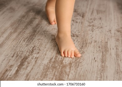 child's feet on the wooden floor close-up