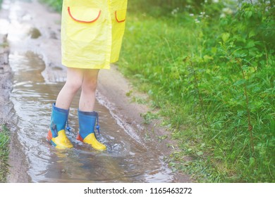 child's feet in a rubber boot in a puddle