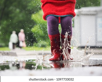 Child's feet in rubber boots. Summer, puddles, rain. The concept of children's recreation, walks in any weather, the health of the child