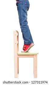 child's feet standing on the little chair on tiptoes on white background