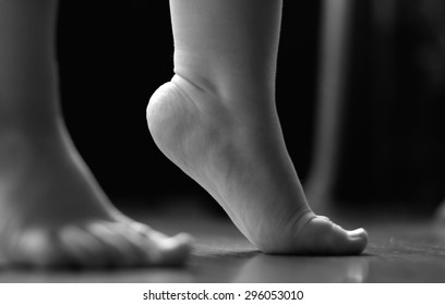 child's feet standing on tiptoes  Black and White