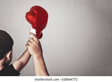 a child's hand in a boxing glove, dad supporting his child to success