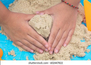 Child's hand close up playing sand at home indoors.