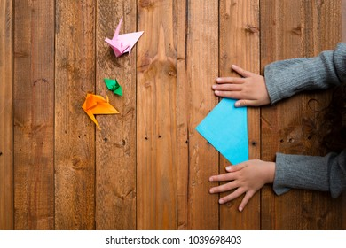 Child's hand to fold origami