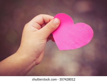 Child's hand giving a heart of paper