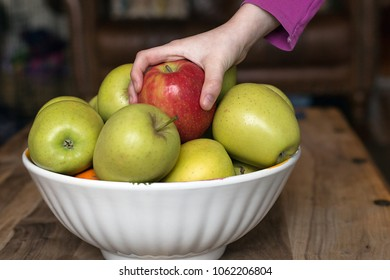 Child's hand grabbing a pink apple from a bowl of apples.