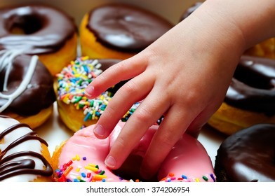 Child's hand grabbing a pink donut from a box of assorted donuts