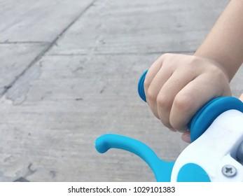 Child's hand  grap handlebar of bicycle.