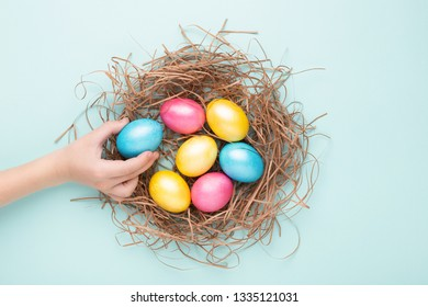 Child's hand holding colorful Easter egg. Eggs in nest on turquoise background. Top view, copy spase, minimal styled.