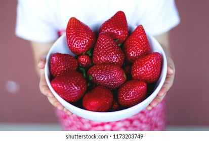 Childs hand holding fresh plate of strawberries on red background, Summer healthy eating concept.