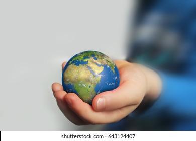 Child's hand holding globe
