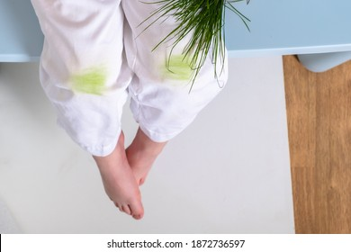 Child's hand holding the grass. dirty grass stains on children's pants. daily life dirty stain for wash and clean concept