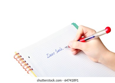 "Child's hand holding ink pen while writing letter to Santa Claus, asking for a Christmas' gift, text ""Dear Santa"" in checkered workbook with copy space for your message, background isolated on white"