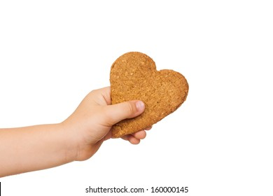 A child's hand is holding a love shaped gingerbread cookie. Isolated on white.