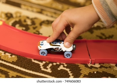 Child's hand holding a toy car.